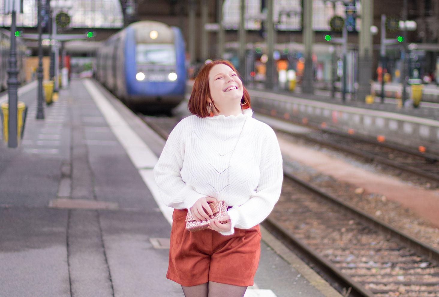 Zoom sur le pull blanc froncé au col et aux manches, avec le sourire dans la gare, avec un sac à paillettes et un short en velours