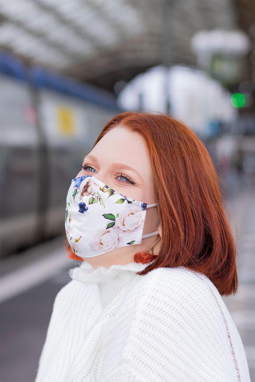 Portrait à la gare, avec un masque aux motifs fleuris porté, avec le sourire