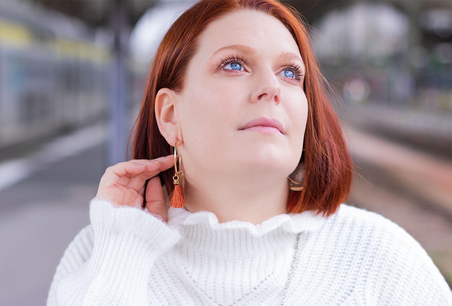 Portrait et zoom sur le make-up avec les yeux bleus, à la gare de Tours, la main dans les cheveux