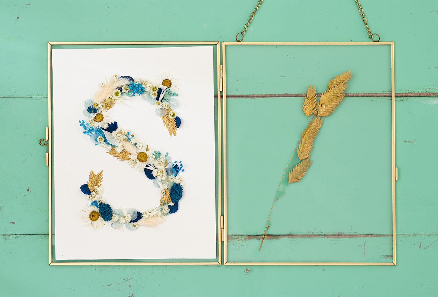 Résultat, posé sur un cadre doré ouvert, de la lettre S réalisée en fleurs séchées