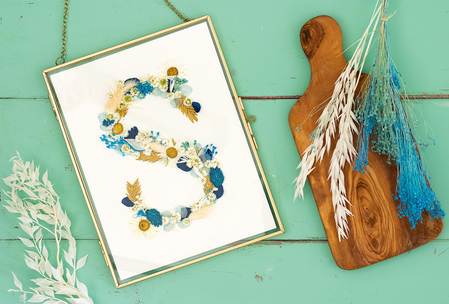 Résultat du DIY facile du cadre de fleurs séchées avec la lettre S, posé sur une table en bois au milieu de fleurs sèches