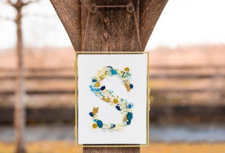 Une lettre en fleurs séchées dans un cadre doré accroché à une poutre en bois