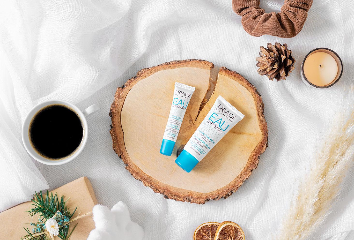 La crème riche et le soin contour des yeux de la gamme hydratation d'Uriage, posés sur un rondin de bois sur un lit, avec un café