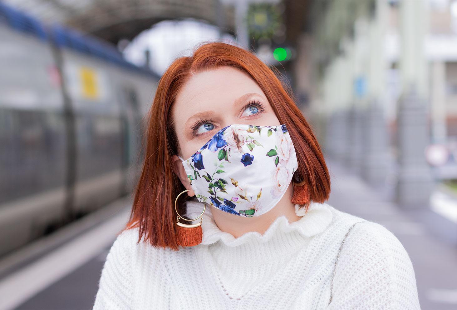 Zoom sur un masque fleuri porté dans une gare