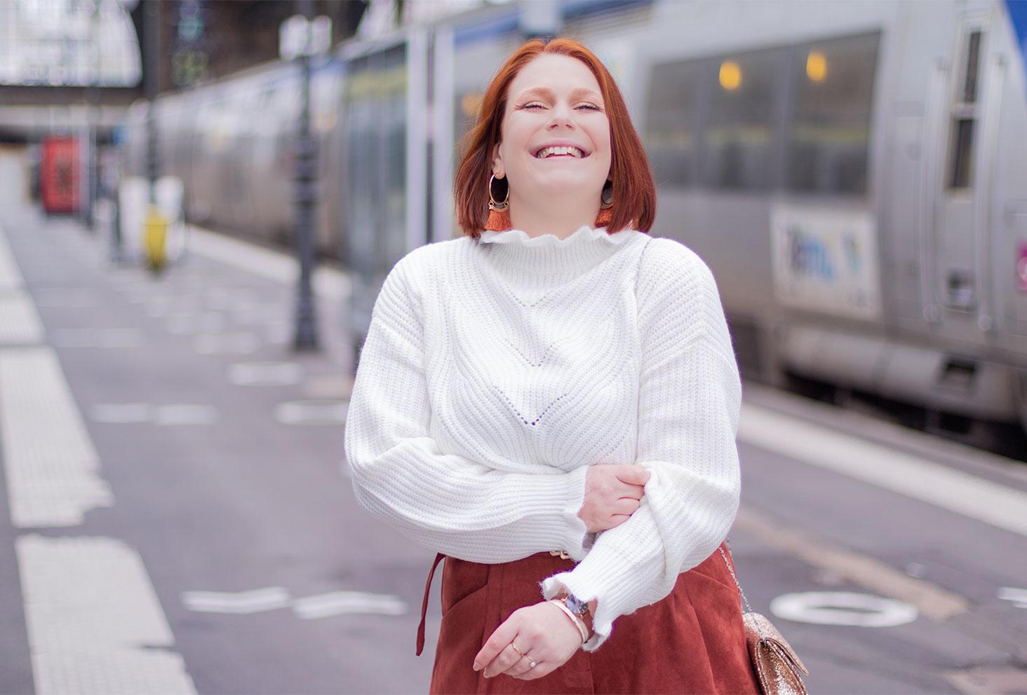 Dans la gare proche des trains, en pull blanc et pochette à paillettes, avec le sourire pour fêter les 5 ans du blog