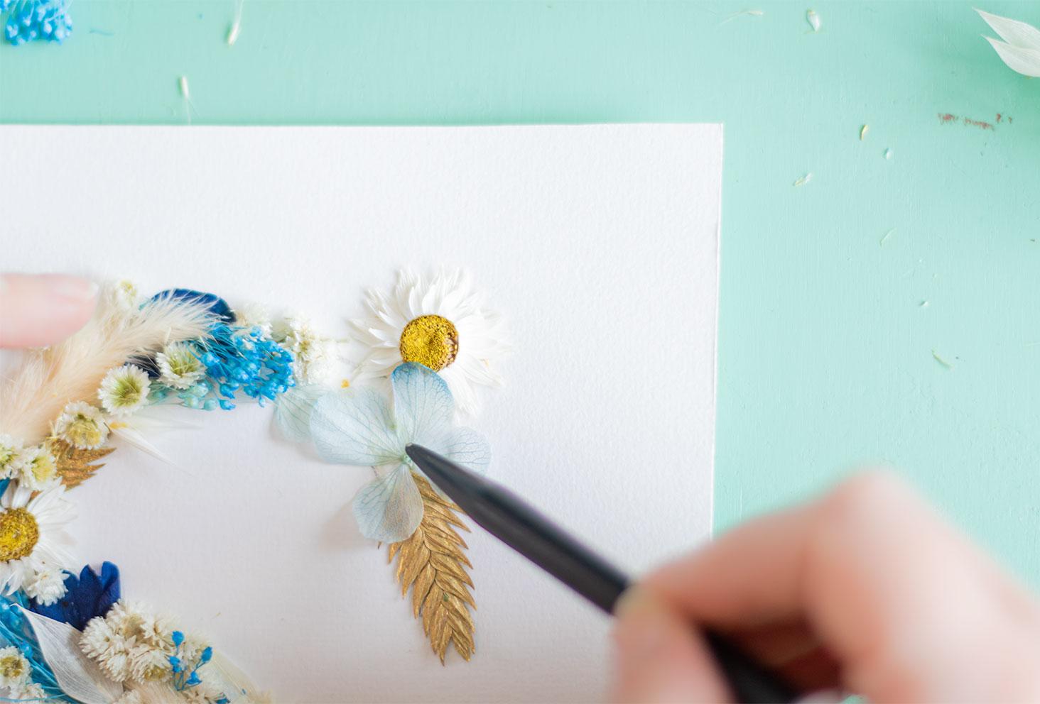 Zoom sur le collage d'un hortensia bleu pastel stabilisé pour terminer la lettre S du cadre de fleurs séchées