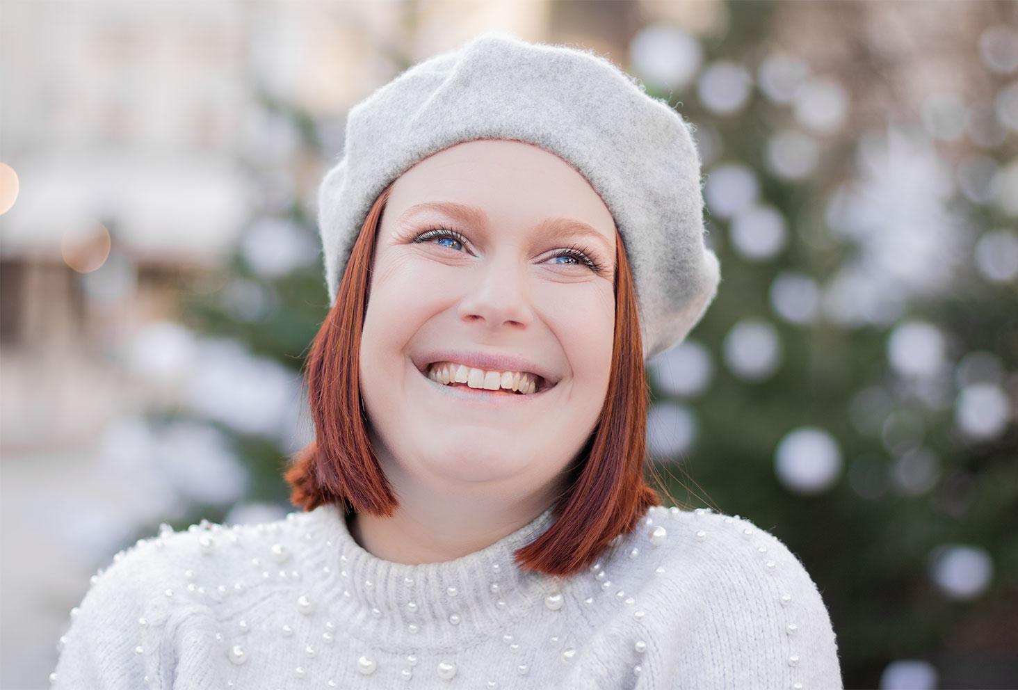 Portrait avec le sourire, un béret sur la tête porté avec un pull gris à perles blanches, devant des sapins de Noël