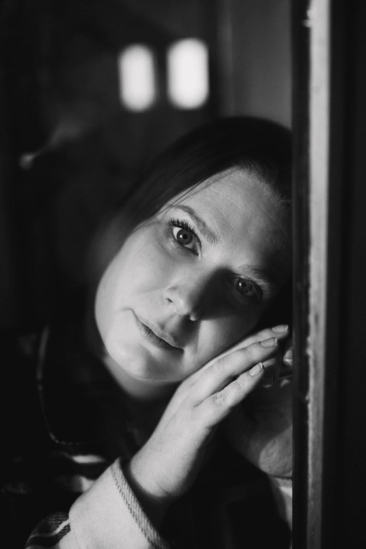 En noir et blanc, derrière le carreau d'une fenêtre, le regard triste