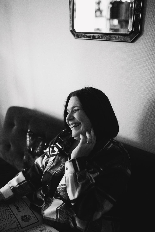 Photographie lifestyle en noir et blanc, avec le sourire, assise dans un canapé