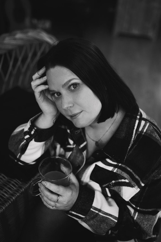 Photo nostalgique en noir et blanc, assise au sol accoudé à un fauteuil, une tasse de café dans la main et le regard dans le vide