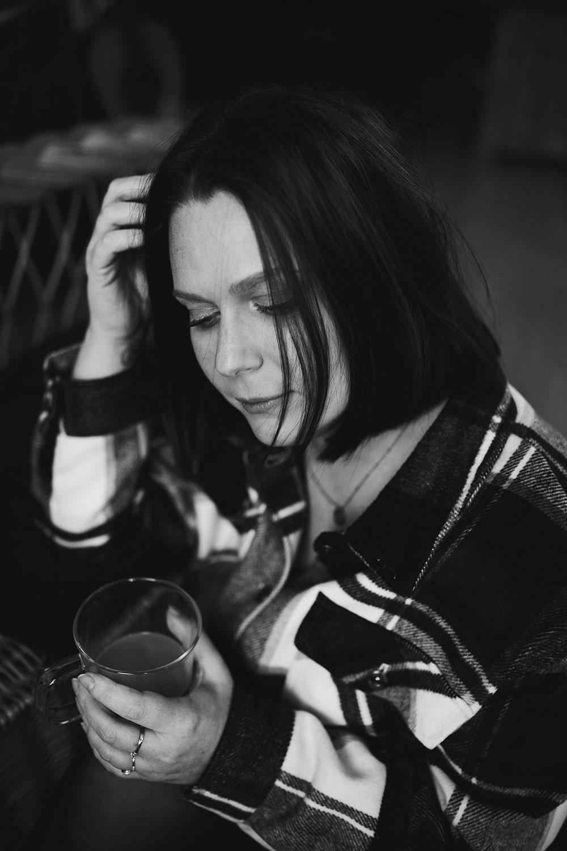 Assise au sol, une main dans les cheveux et l'autre tenant une tasse de café, en noir et blanc