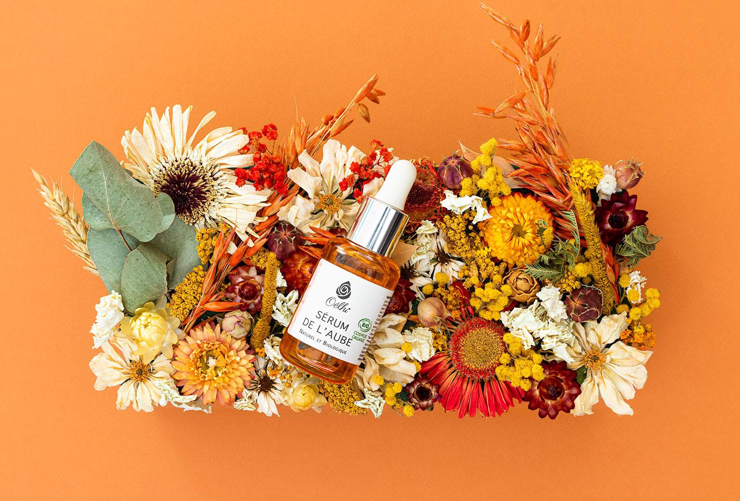 Zoom sur le sérum de l'Aube de la marque Oélhi, posé sur une composition de fleurs séchées orangées de le même couleur que le flacon
