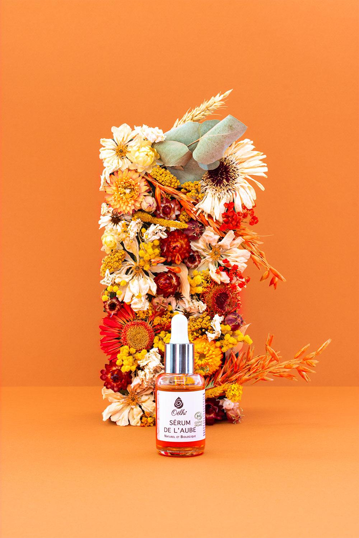 Le sérum visage de jour Oélhi posé sur un fond orange devant un mur végétal de fleurs séchées