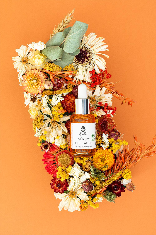 Le sérum de l'Aube pour le visage de la marque Oélhi posé sur une composition en fleurs sèches
