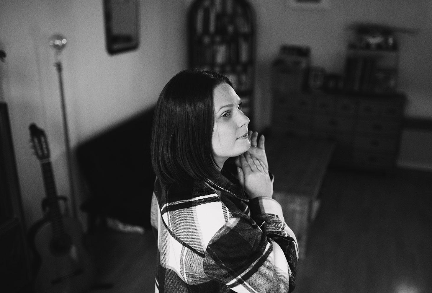 Photo lifestyle en noir et blanc, au milieu d'un salon, dans une chemise à carreaux