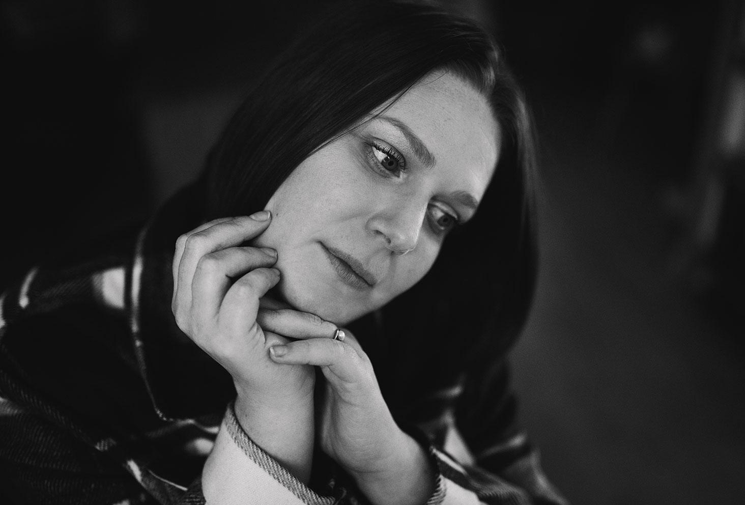 Le regard nostalgique, en noir et blanc, assise sur le sol, les mains sur le visage