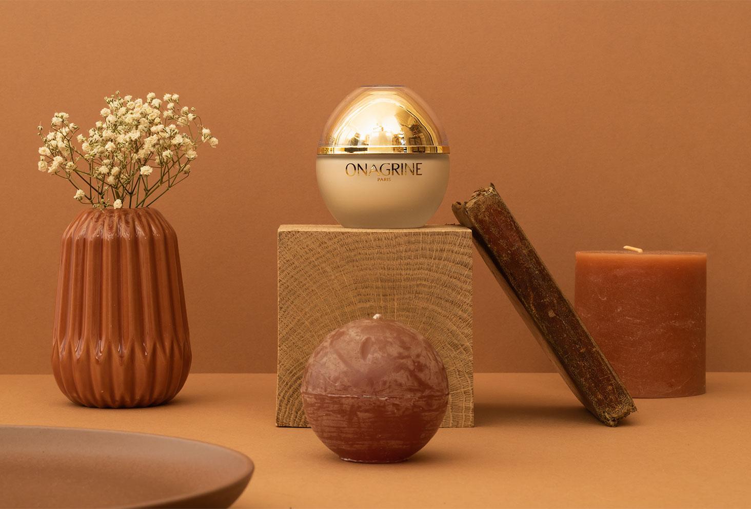 La crème aux 20 huiles précieuses Onagrine dans son packaging doré, posé sur un cube en bois dans une mise en scène géométrique