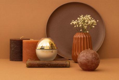 La crème hydratante au 20 huiles précieuses Onagrine, dans son flacon doré, posé sur un livre ancien au milieu d'un décor géométrique marron