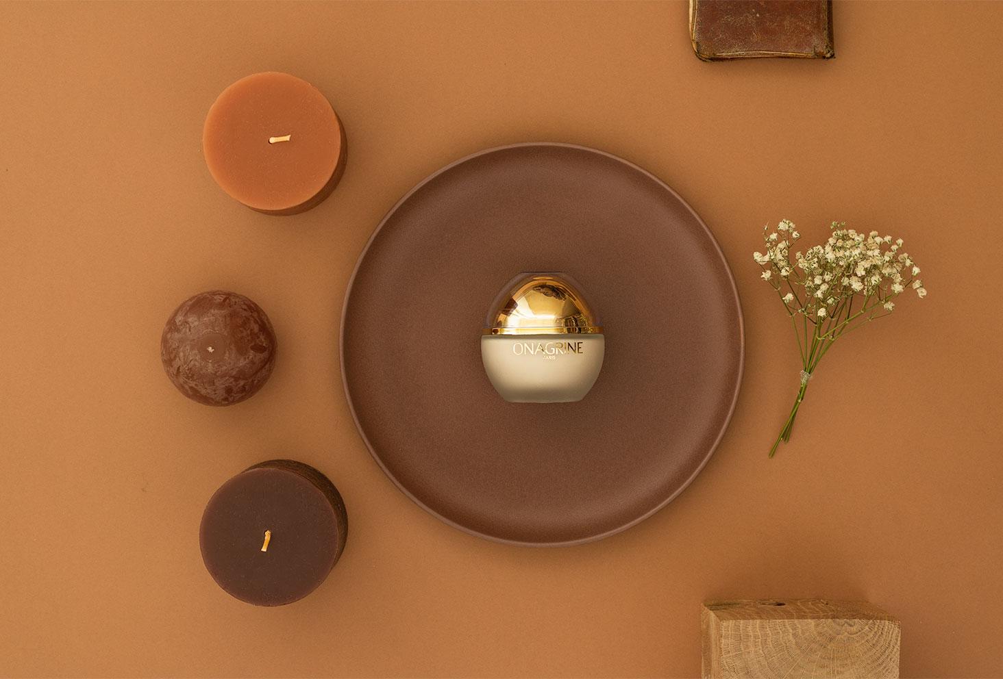 Zoom sur le packaging doré de la crème aux 20 huiles précieuses, posée dans une assiette marron au milieu d'un stylisme photo géométrique