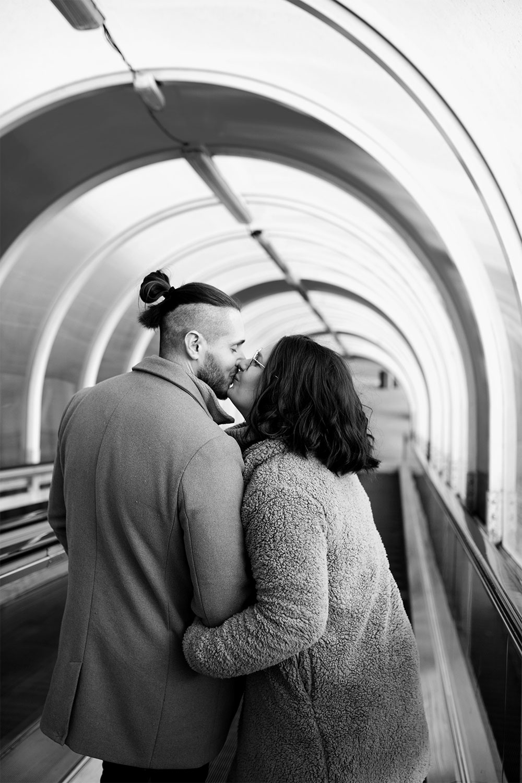 Photo de couple en noir et blanc, de dos main dans la main au milieu d'un escalator