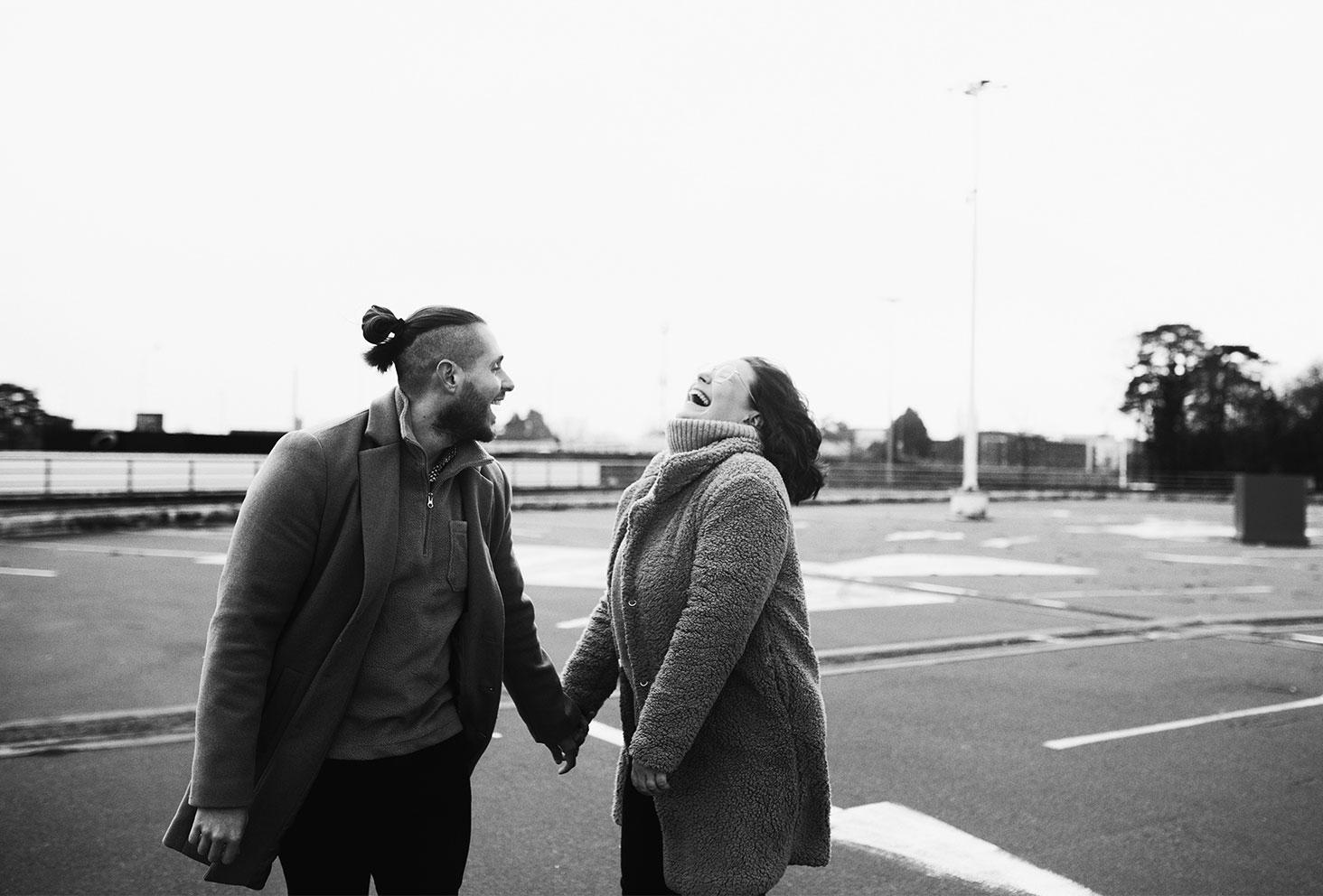 En amoureux main dans la main, en riant aux éclats, au milieu d'un parking en noir et blanc
