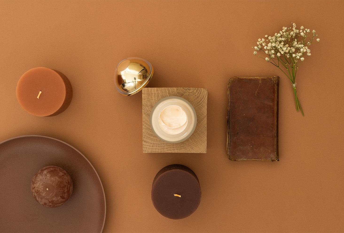 Mise en avant de la texture de la crème hydratante précieuse Onagrine, dans un décor marron et géométrique