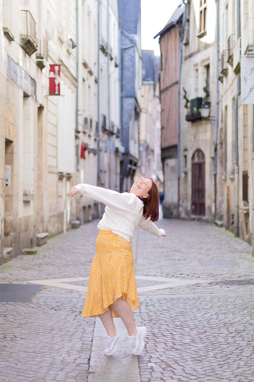 Look chill en jupe fluide et baskets, au milieu d'une rue de centre ville, dans une figure de danse