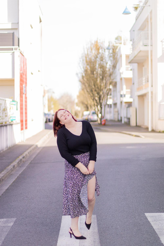 En centre ville sur un passage piéton en jupe asymétrique noire, avec le sourire et une jambe relevée au travers de la fente de la jupe