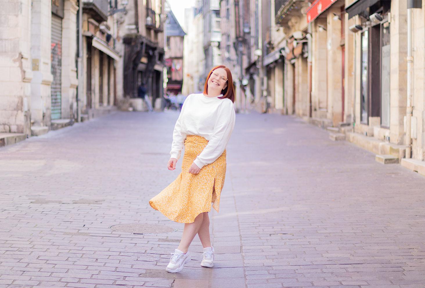 Jupe fluide et jaune La Halle, portée avec le sourire en plein centre ville, avec un sweat aux épaules bouffantes blanc