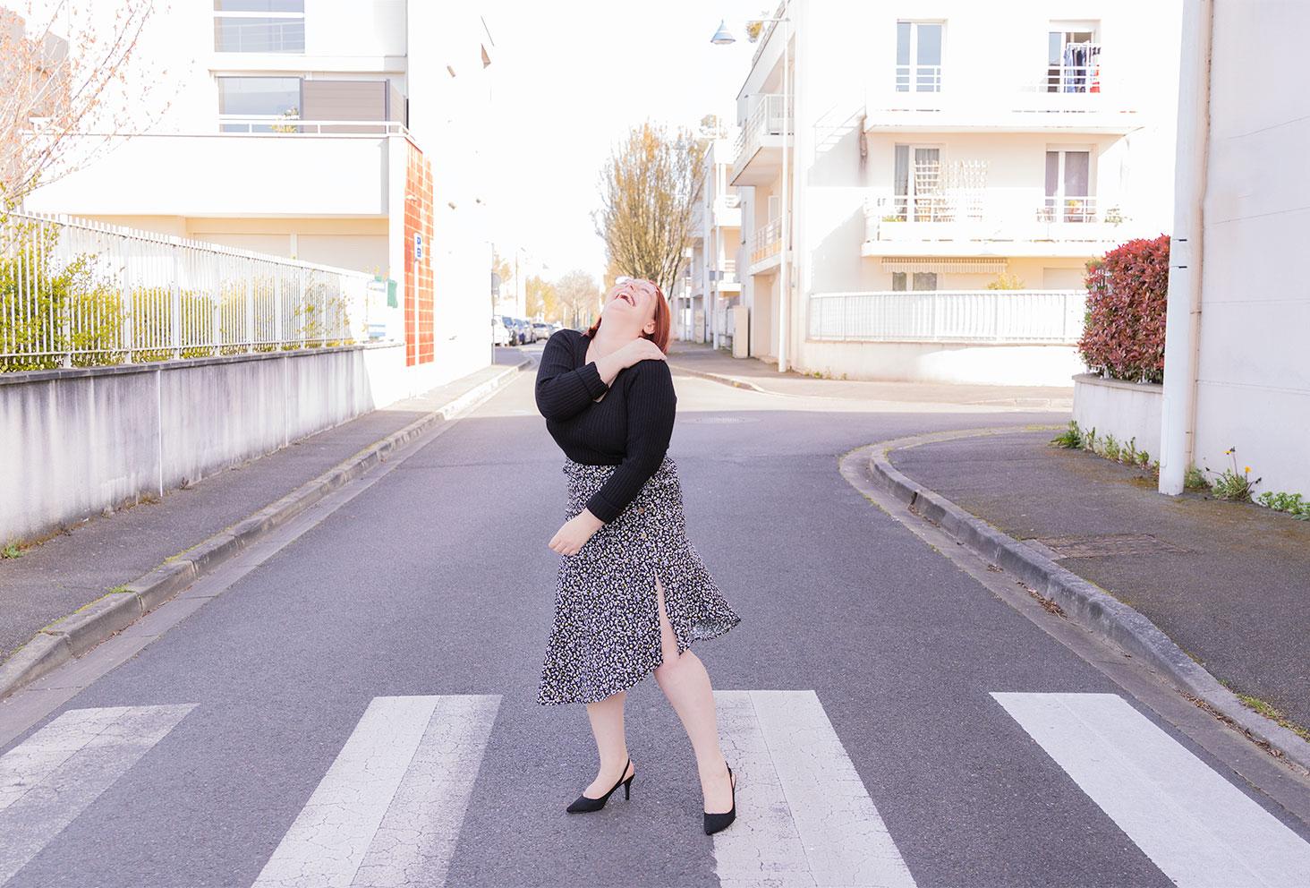 Rire et dans sur un passage piéton en plein centre ville, en jupe fluide noire et blanche fendue sur le côté, avec des talons noirs et un pull fin