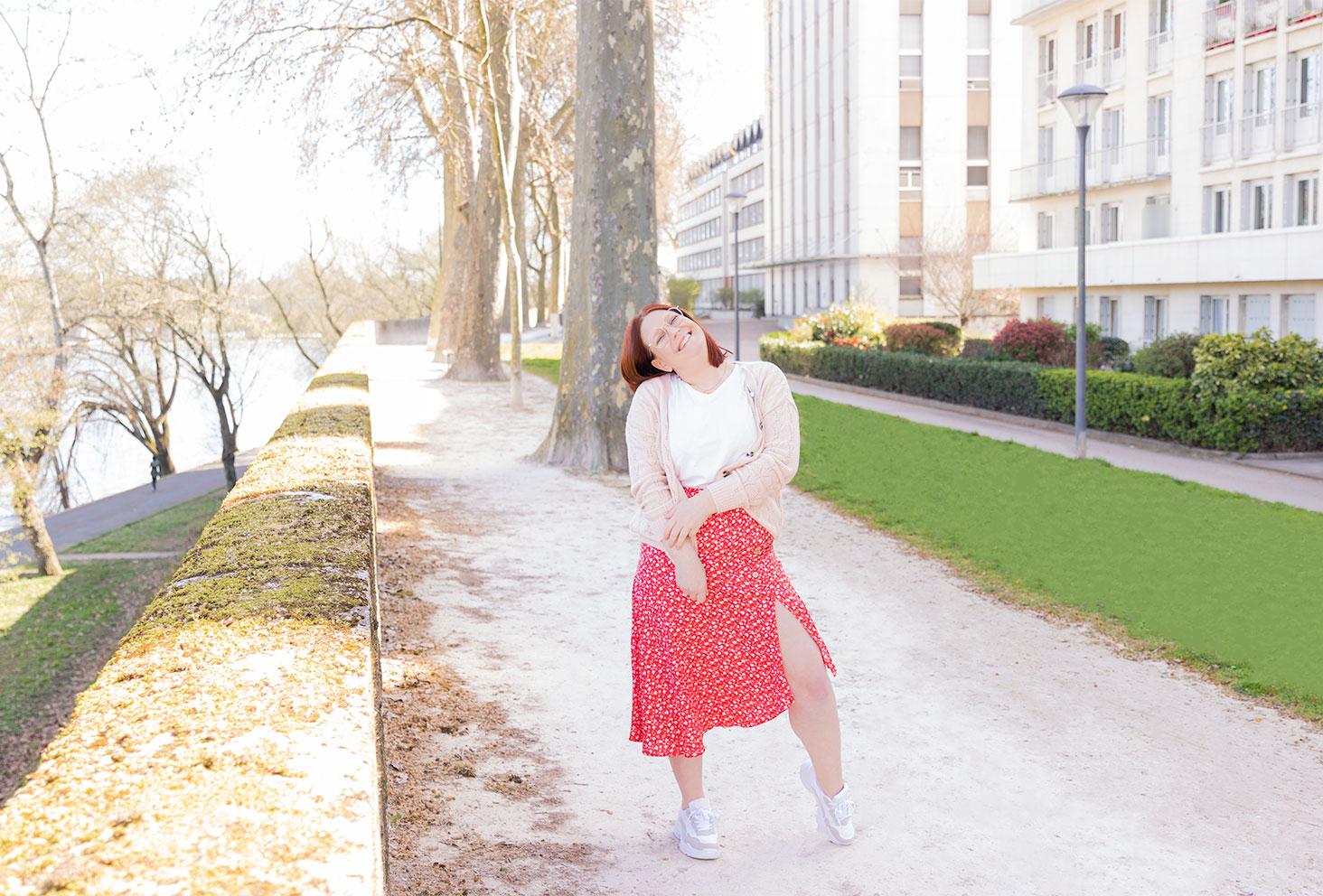 Jupe asymétrique rouge, gilet rose pastel et t-shirt blanc, avec une paire de baskets sur les bords de Loire
