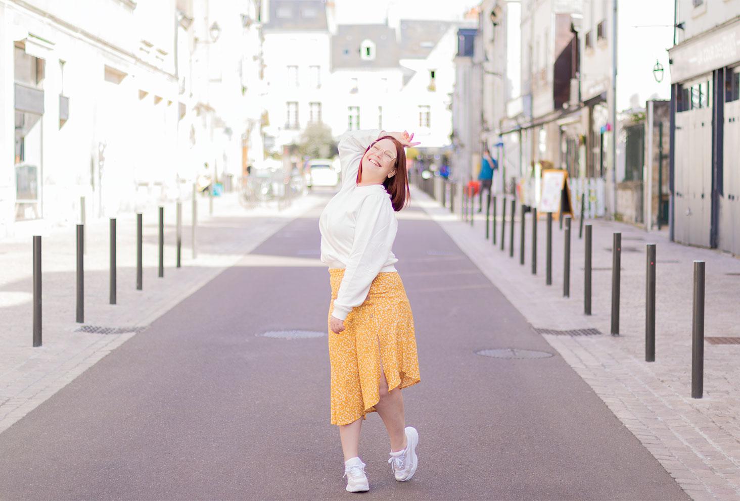 Jupe jaune fluide et asymétrique La Halle, portée avec un gros sweat blanc et une paire de baskets, pour un look chill avec le sourire