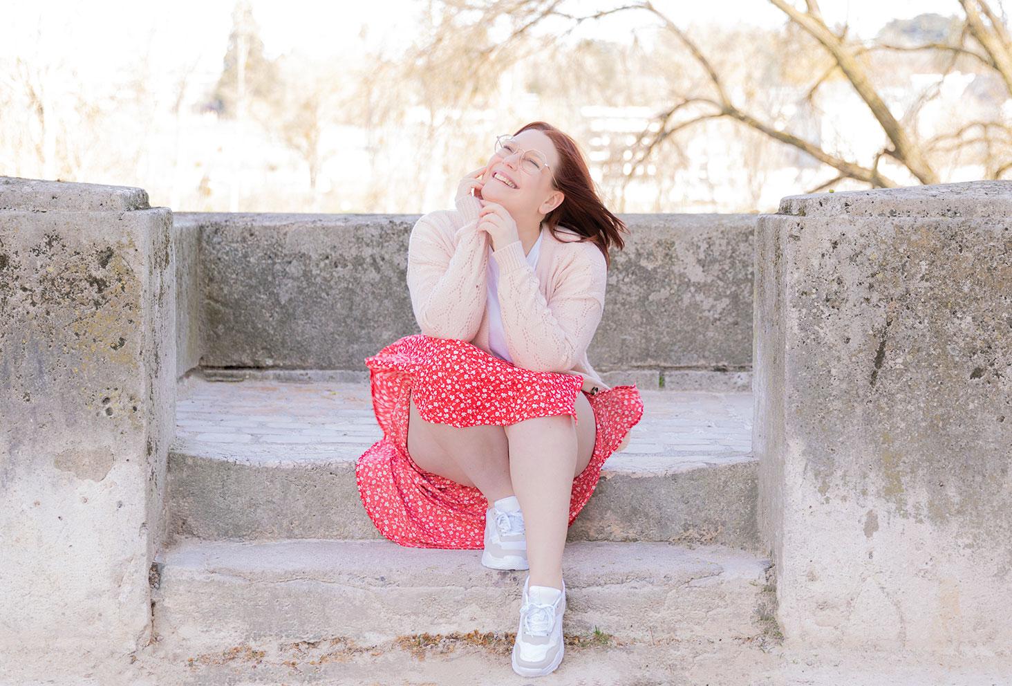 Assise sur des marches en pierre avec le sourire, en jupe fluide qui vole au vent et gilet rose pastel en maille fines