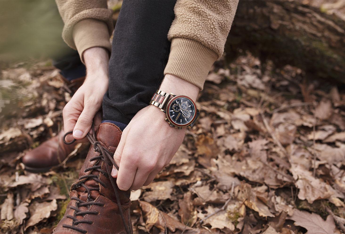 Zoom sur la montre en bois Nordic Wood Ceiba portée, en train de faire les lacets des boots en cuir marron