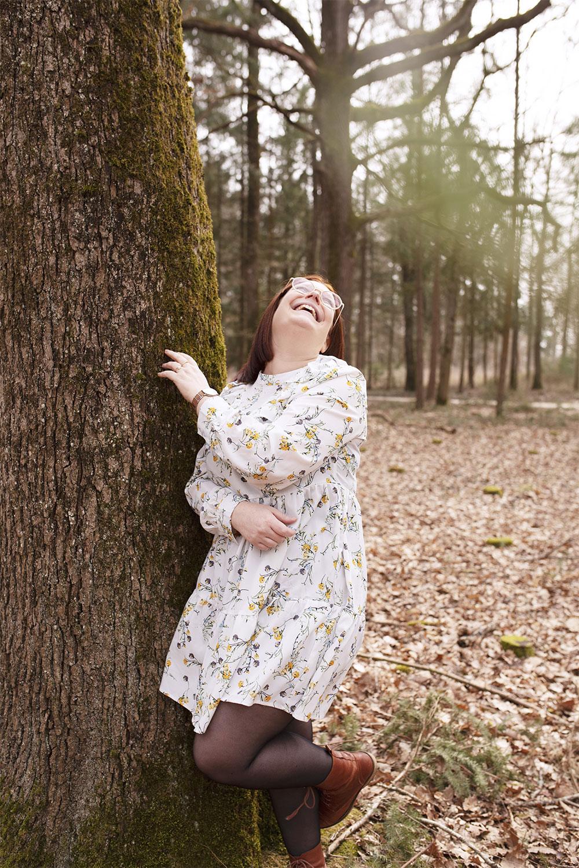 Dans la forêt, appuyée contre un arbre, en robe fleurie avec le sourire