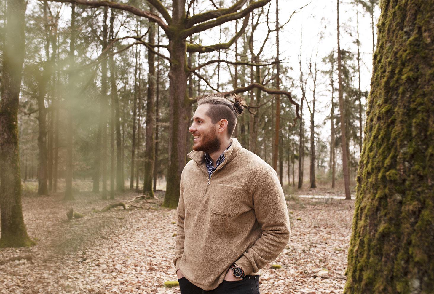 Tristan dans la forêt en pull camionneur beige, avec le sourire et les mains dans les poches