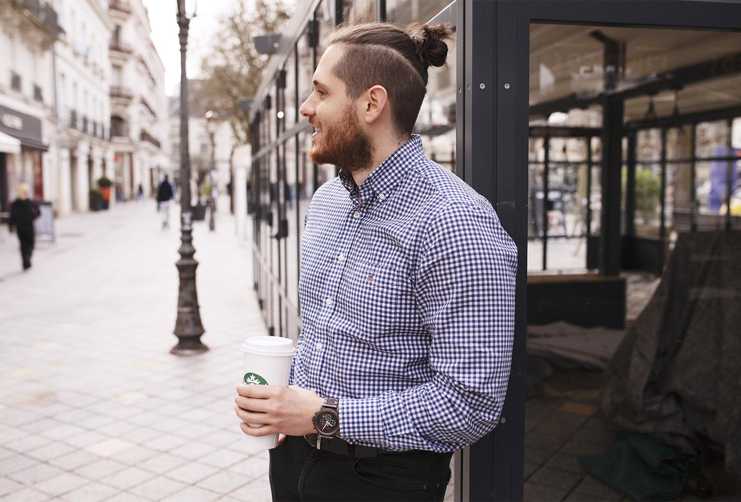 En chemise à carreaux avec un Starbucks dans les mains, en centre ville appuyé contre un bâtiment en verre