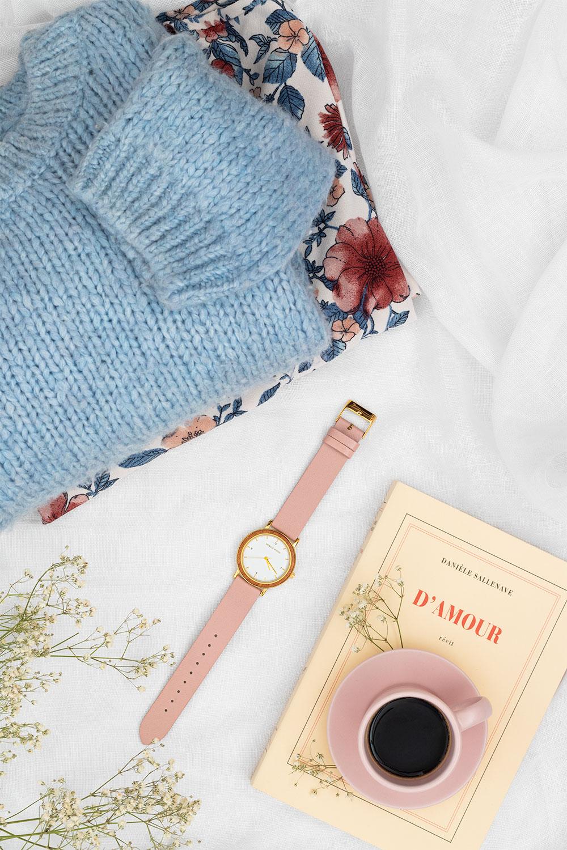 Mise en avant de la montre en bois et en cuir Pure Pink dans un doux décor pastel rose et bleu