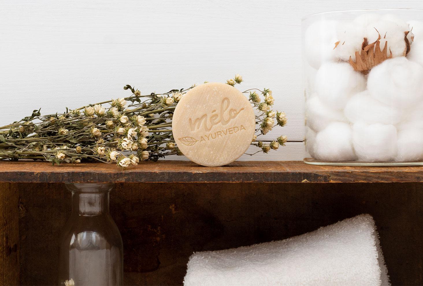 Zoom sur le shampoing solide pour cheveux gras Mélo Ayurveda posé sur une étagère en bois avec des fleurs et du coton
