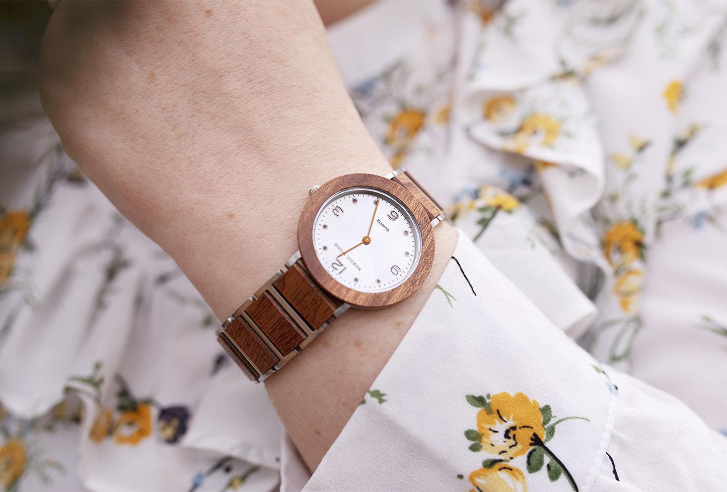 Zoom sur la montre en bois Anémone de la marque Nordic Wood portée au poignet avec une robe à fleurs
