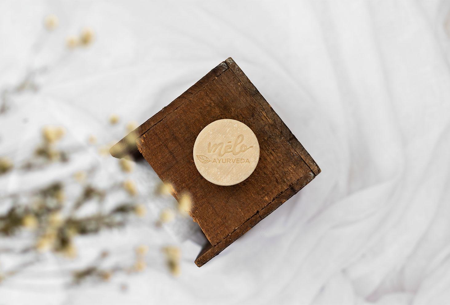 Zoom sur le shampoing solide dédié aux cheveux gras de la marque Mélo Ayurveda, posé sur un support en bois