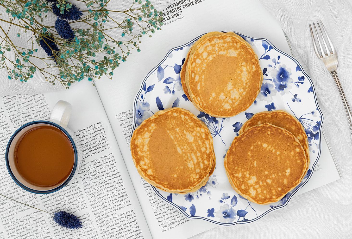 Des pancakes moelleux à la banane dans une assiette vintage, posée sur un magazine ouvert, avec un thé et des fleurs séchées