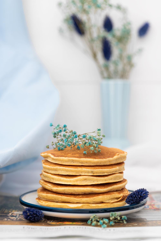 Pancakes moelleux à la banane dans une assiette bleu au milieu de fleurs séchées