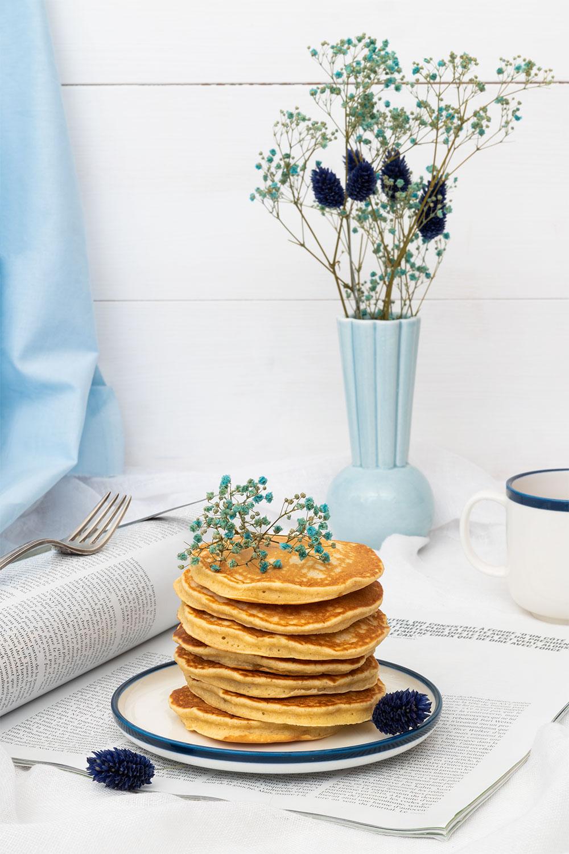 Des pancakes moelleux dans une assiette, sur un magazine, dans un décor bleu et fleuri