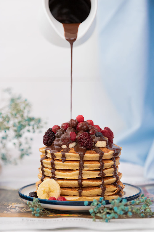 Des pancakes moelleux à la banane recouverts de fruits rouges et de bananes, sur lequel on verse un coulis de chocolat au lait