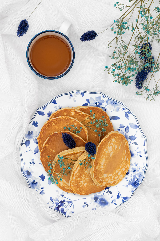 Des pancakes moelleux à la banane dans une assiette fleurie, avec des fleurs séchées bleues, sur un lit avec un thé