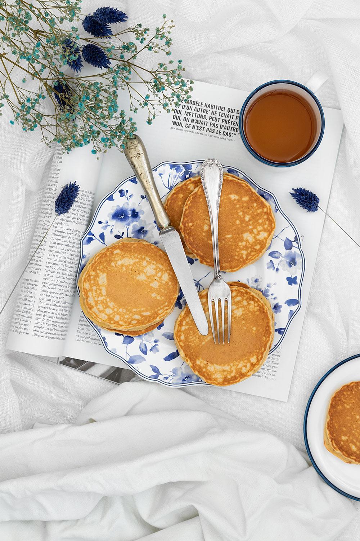 Des pancakes moelleux à la banane sur un lit, dans une assiette avec des couverts et un thé, près à être mangés