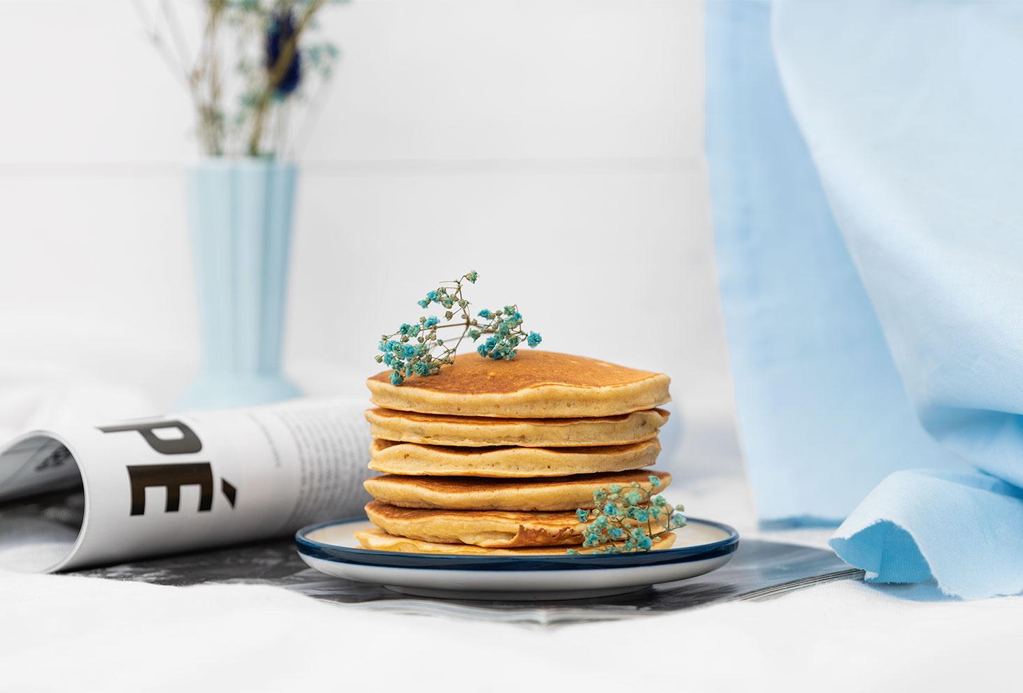 Pancakes moelleux à la banane dans une assiette, au milieu d'un décor bleu