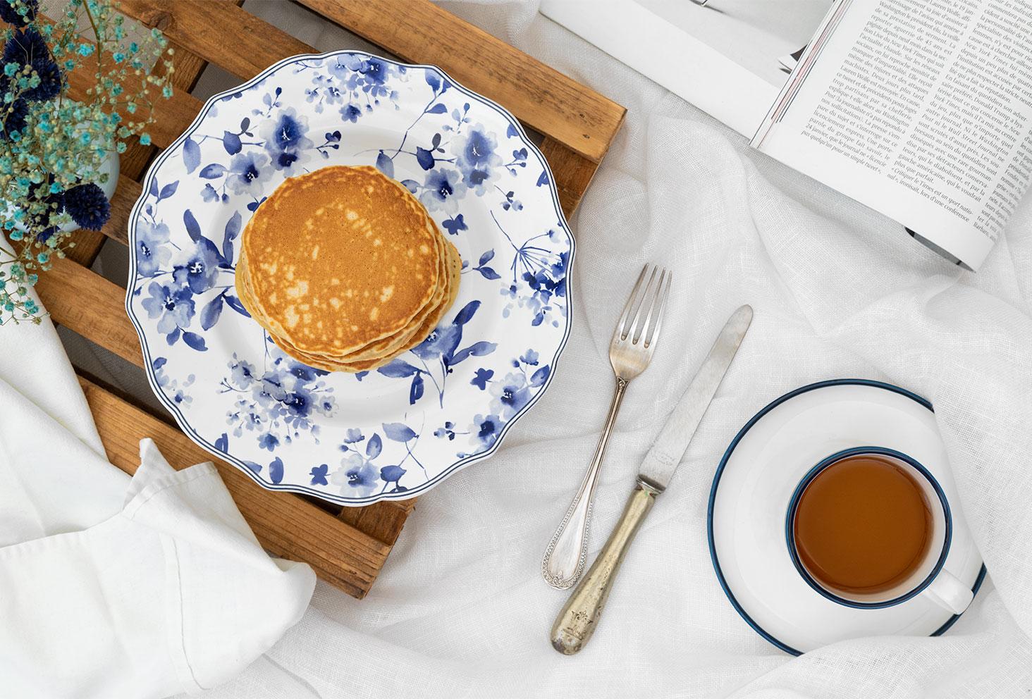 Des pancakes dorés et moelleux à la banane, dans une assiette vintage, sur un lit avec une tasse de thé et un magazine