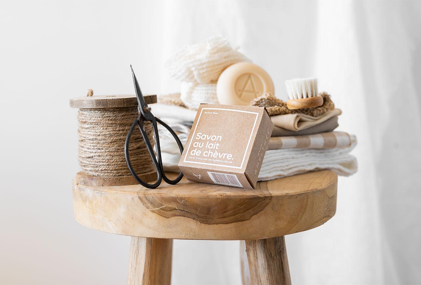 La savon au lait de chèvre de Soin Amalthée dans son emballage kraft, posé sur un tabouret en bois dans une salle de bain